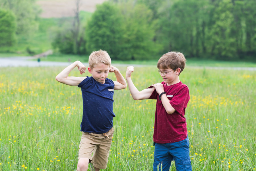 two brothers flexing muscles