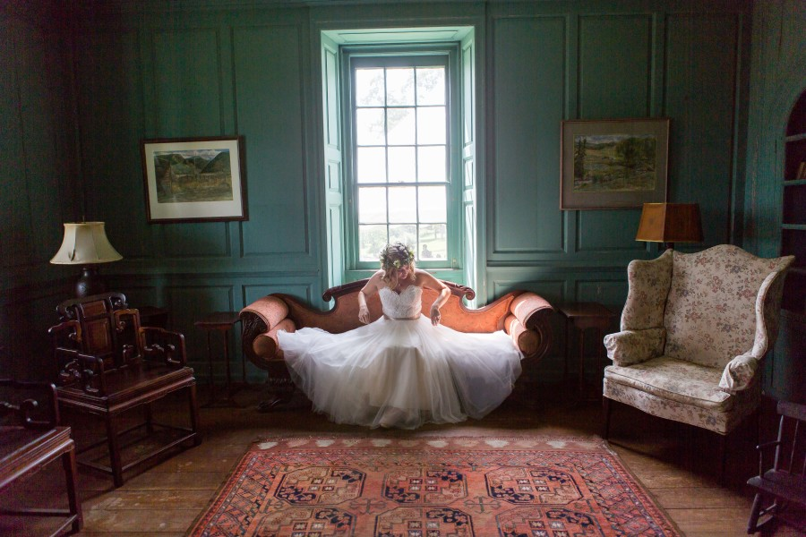 bride sitting in from of large window on antique sofa
