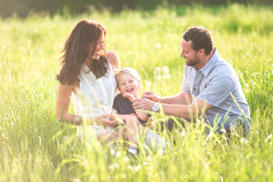 family of three laughing in sunshine