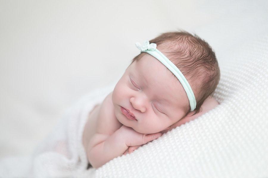 newborn girl sleeping on white blanket