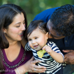parents kissing one year old baby on head