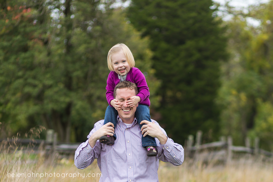 little girl on dads shoulders putting hand in his face