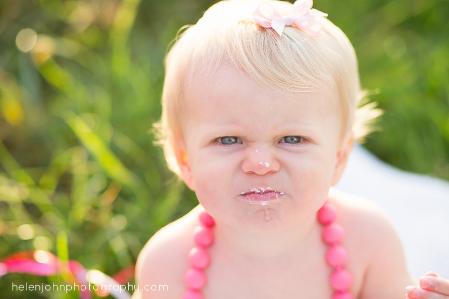 little girl making mean face with cake on her lips