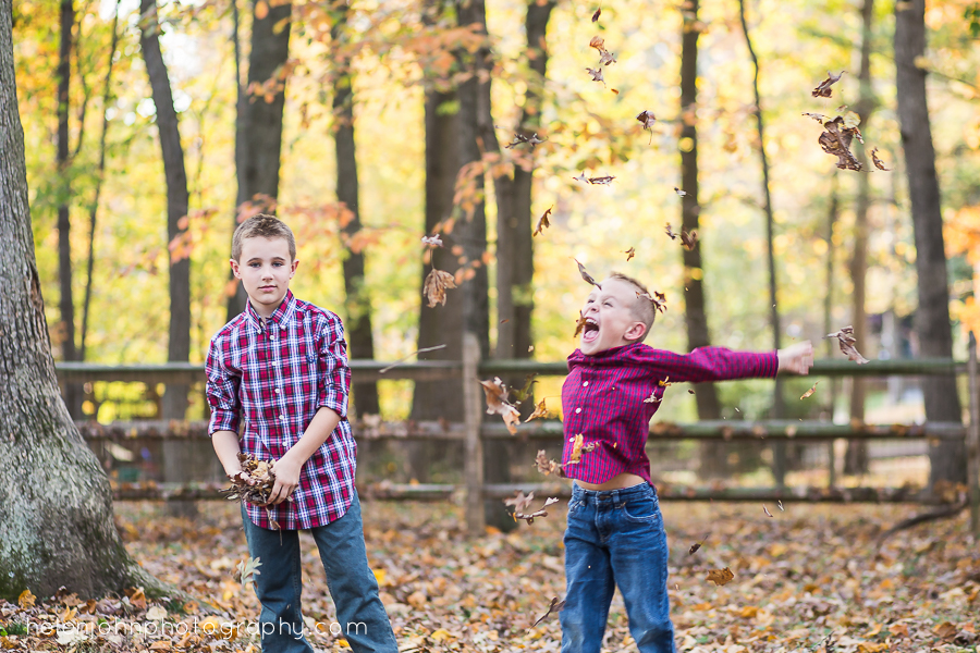 little boy excited throwing leaves in the air