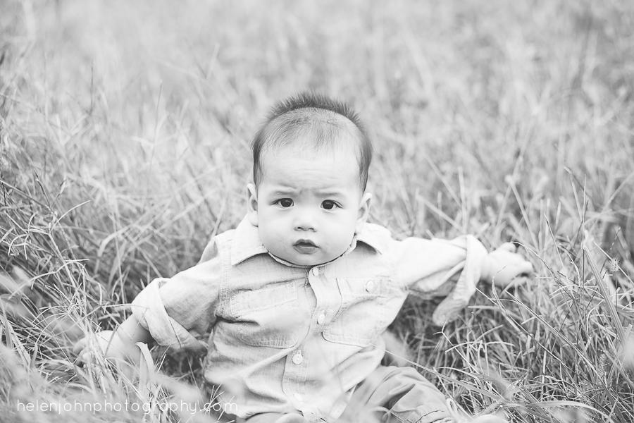 baby boy sitting in feild looking grumpy