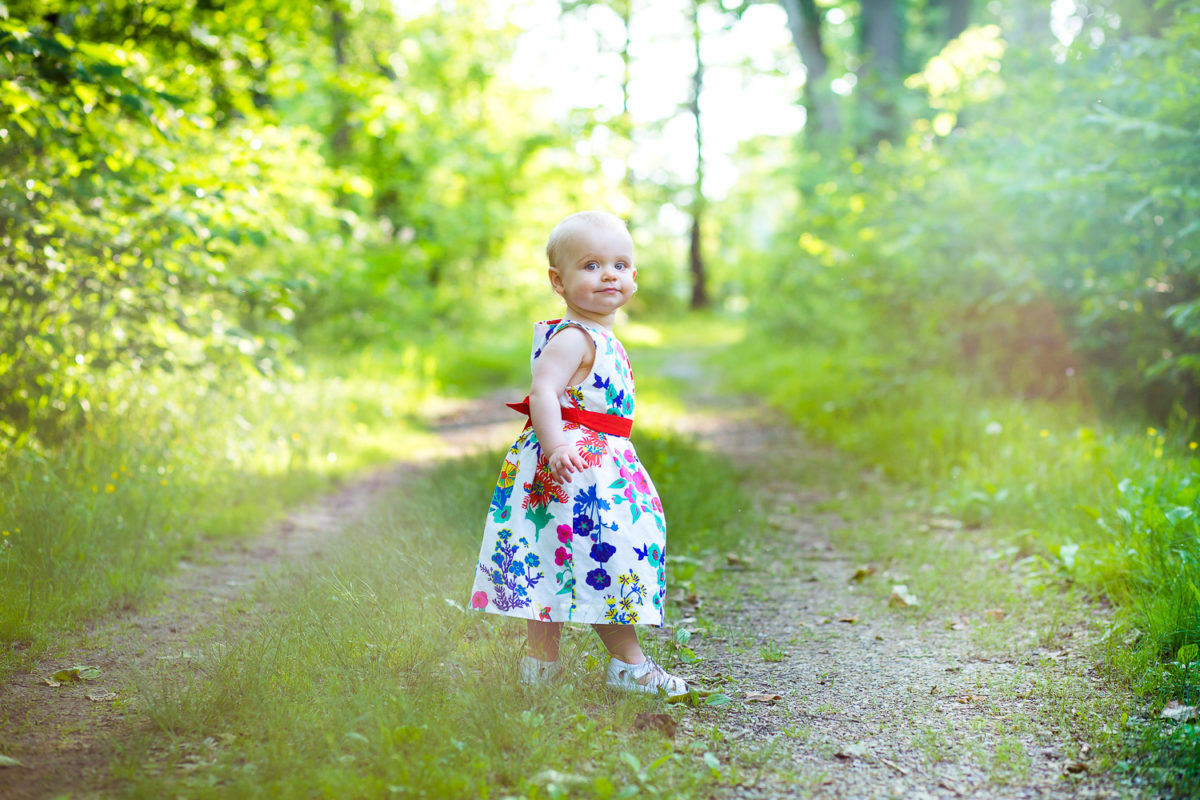 baby girl walking down dirt path