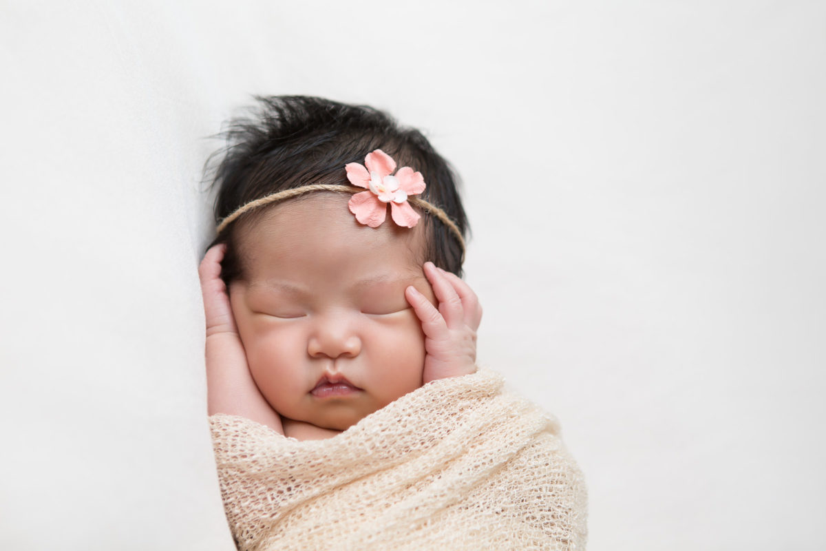 adorable newborn baby girl holding her face