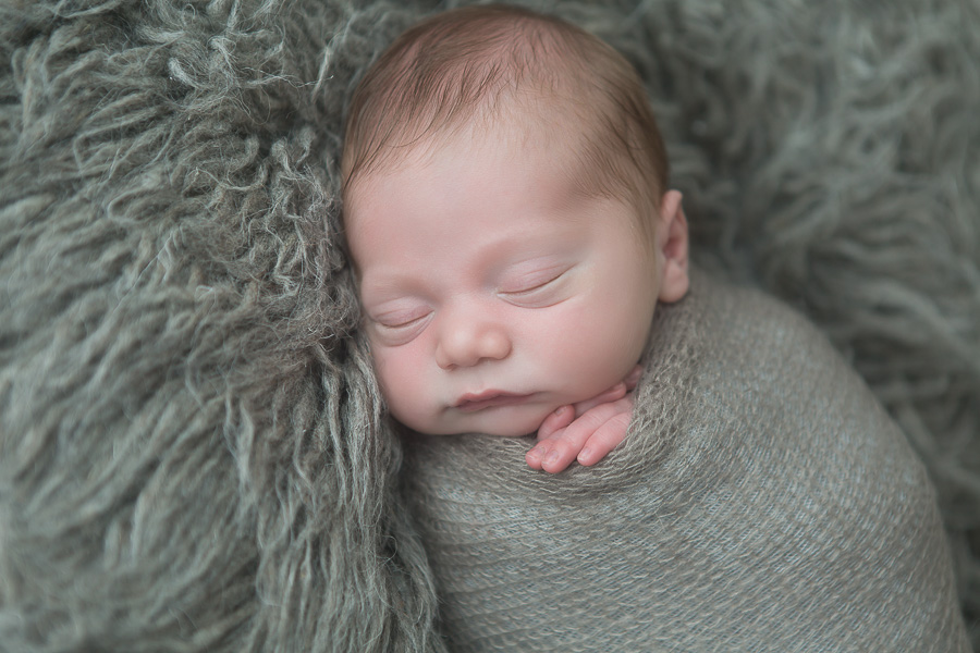 close up of 7 day old baby boy sleeping on grey gur