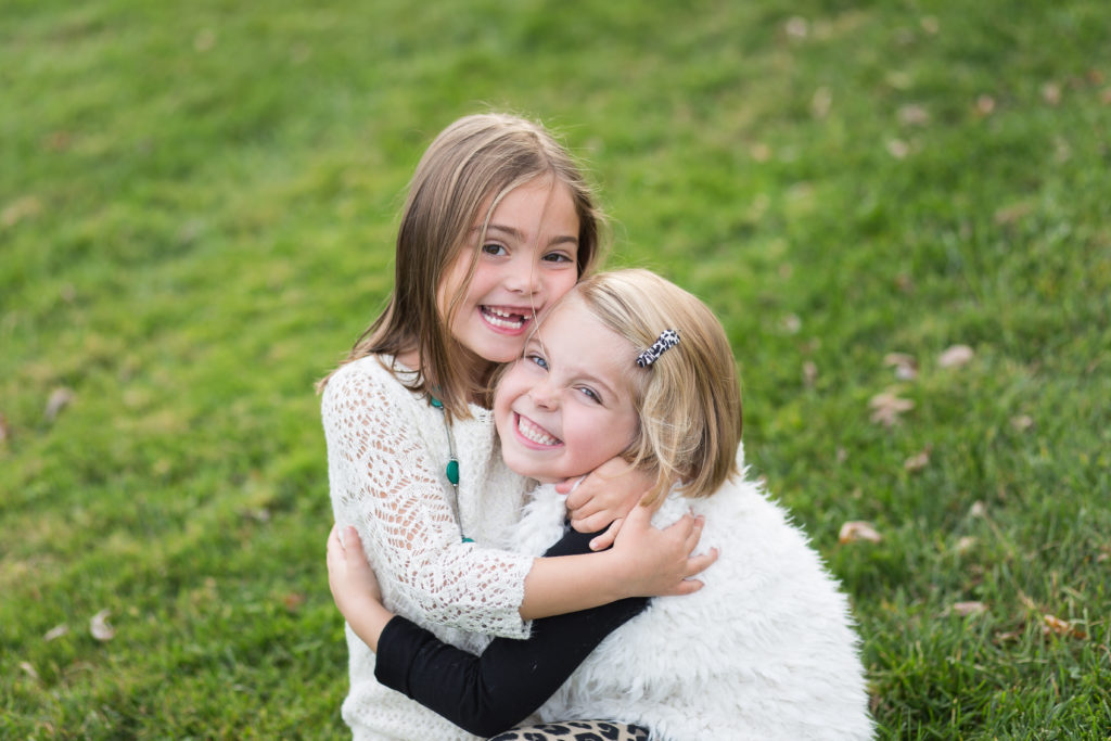 little girl sisters hugging in the grass