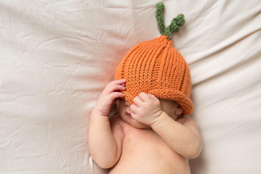 baby pulling hat over face