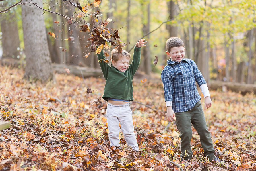 toddler throwing leaves with funny face