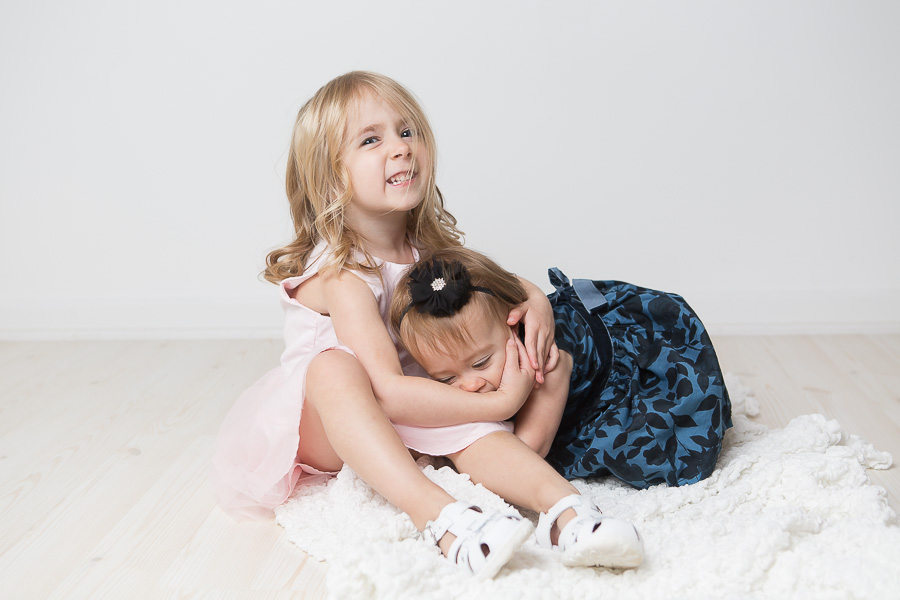 big sister squeezing baby sister