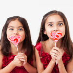 little girls with heart shaped lollipops laughing