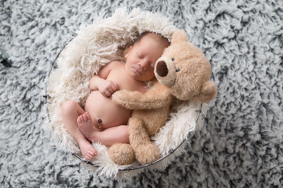newborn boy sleeping with teddy bear