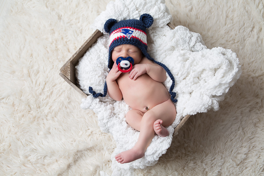 newborn baby with patriots hat and paci