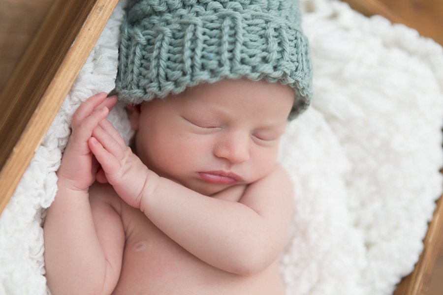 newborn boy sleeping in blue knit hat