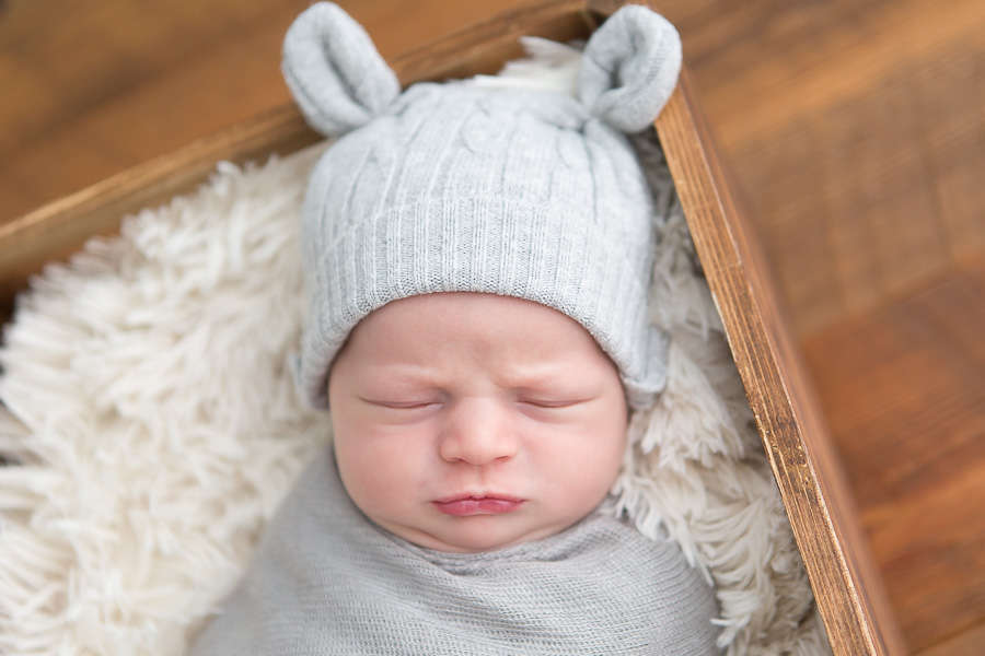newborn boy making grumpy face in bear hat