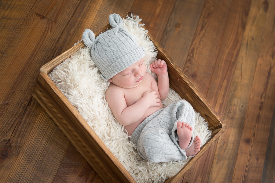 newborn boy sleeping in wooden crate