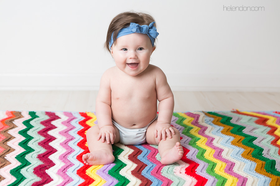 6 month old baby sitting on colorful chevron blanket