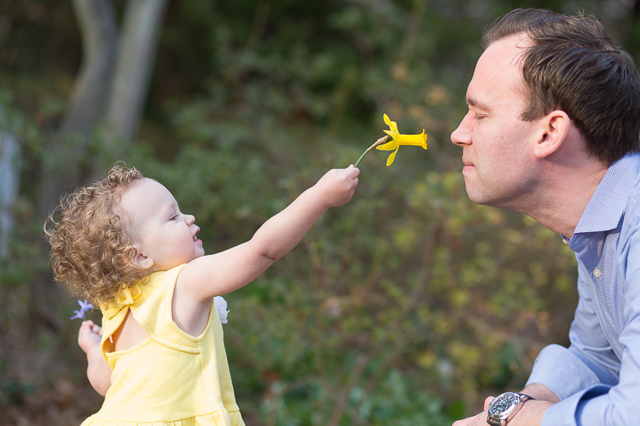 little girl putting flower up to dads nose to smell
