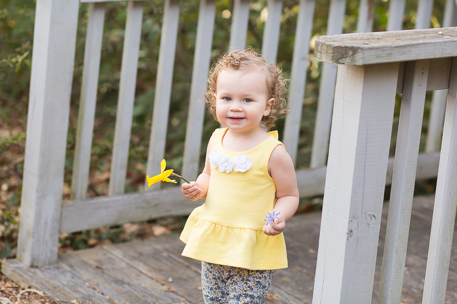 one year old girl holding daffodil laughing