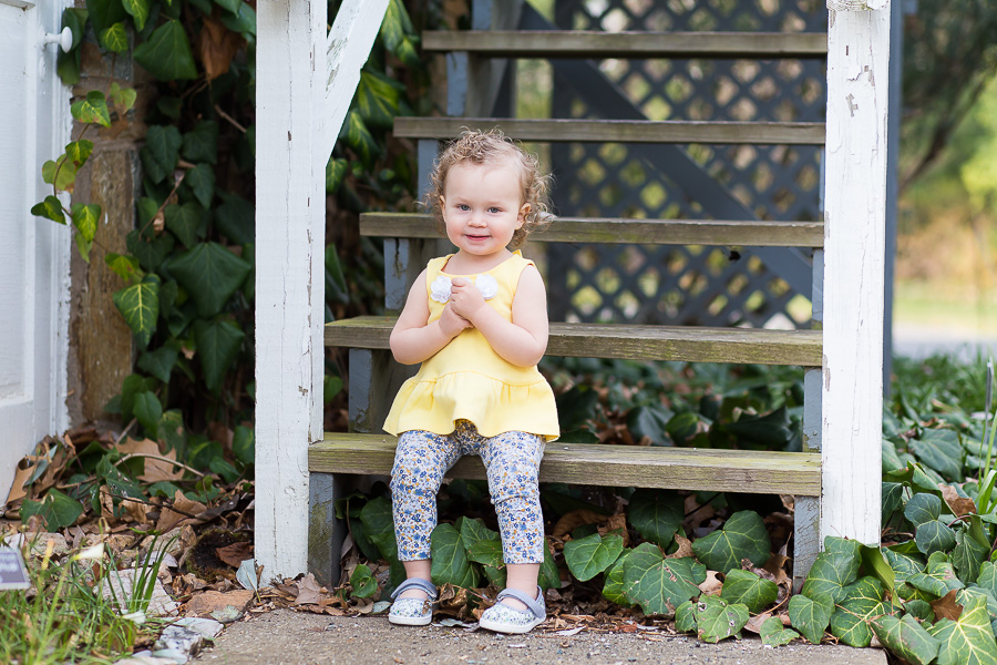 one year old sitting on steps smiling