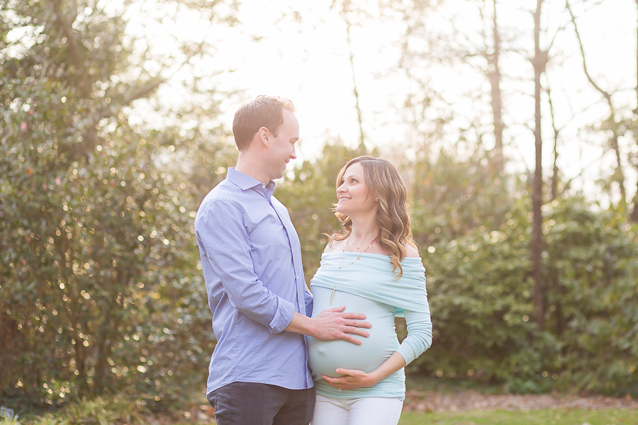 pregnant couple smiling at each other