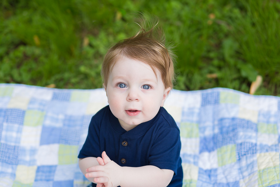 9 month old baby boy with long hair smiling