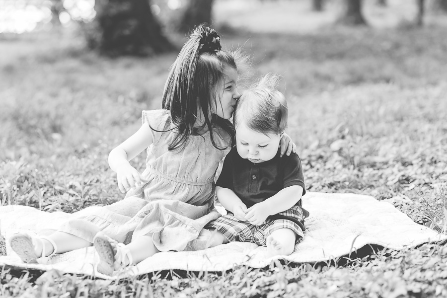 b&w of 3 year old sister kissing baby brother on head