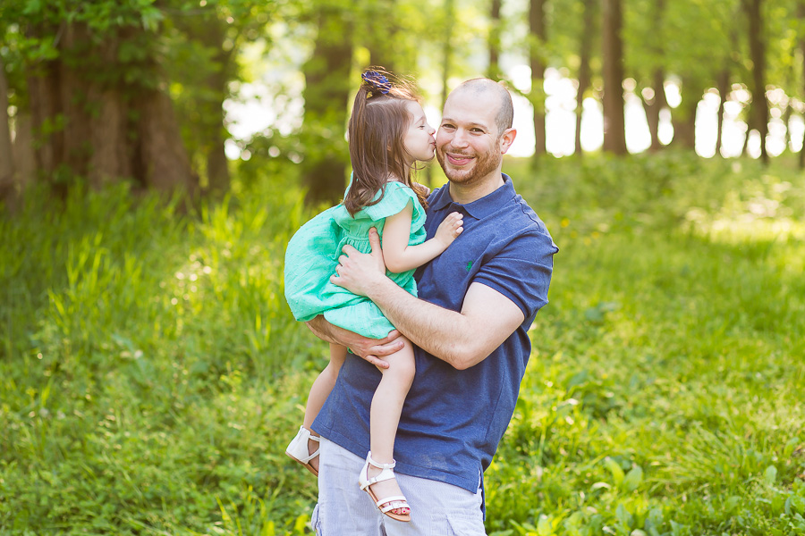 portrait of three year old girl kissing dad on cheek with sunflare