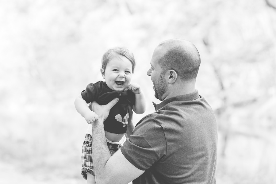 b&w of dad holding laughing baby boy