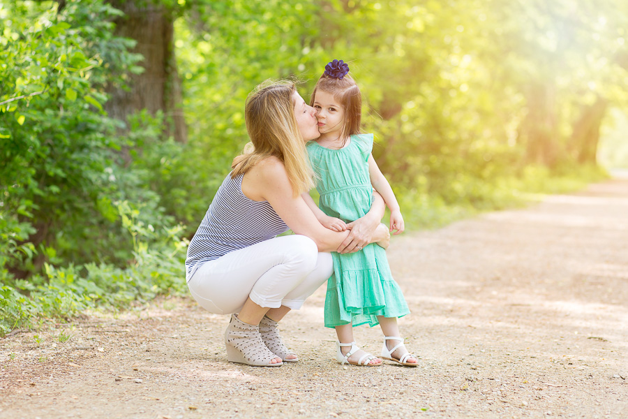 outdoor portrait of mom kissing daughter with sunflare