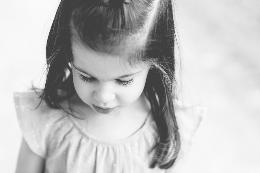 3 year old girl looking down long eyelashes b&w
