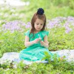 little girl in green dress sitting in purple flowers