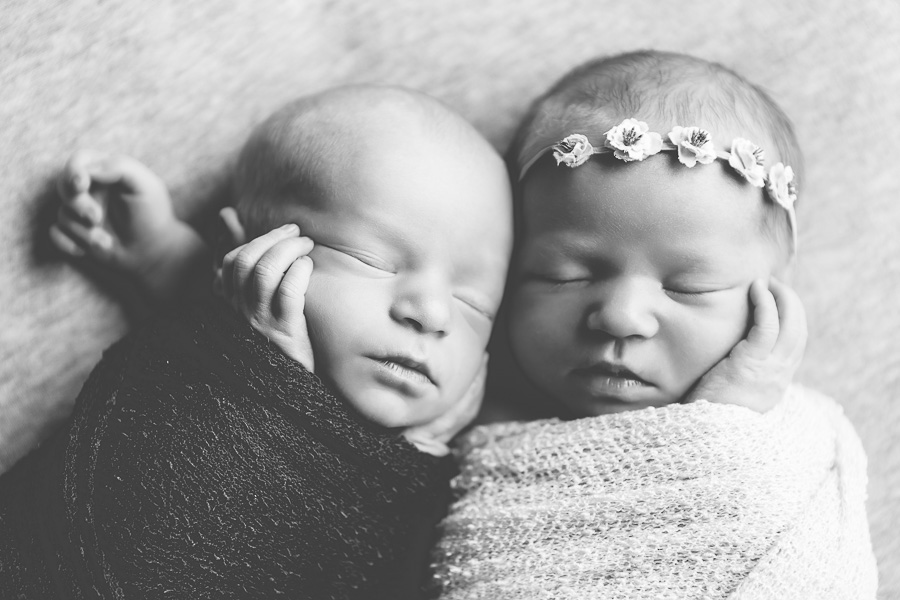 newborn twins sleeping together black & white image
