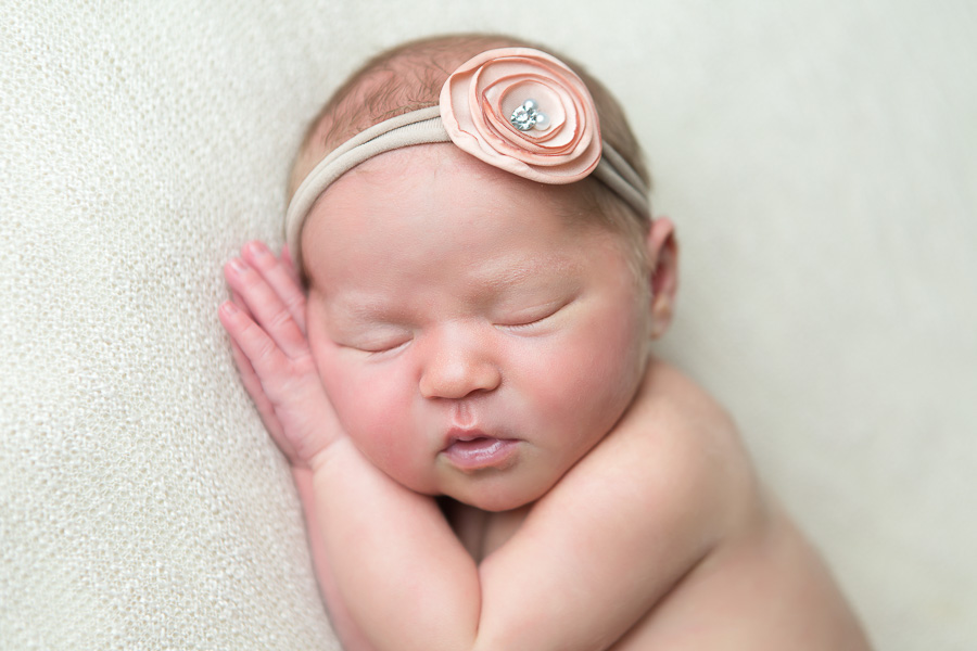 adorable chubby 6 day old baby girl sleeping on hands