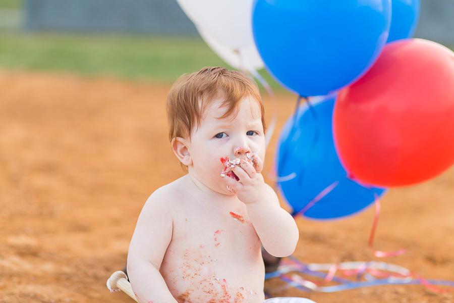 messy baby boy eating cake