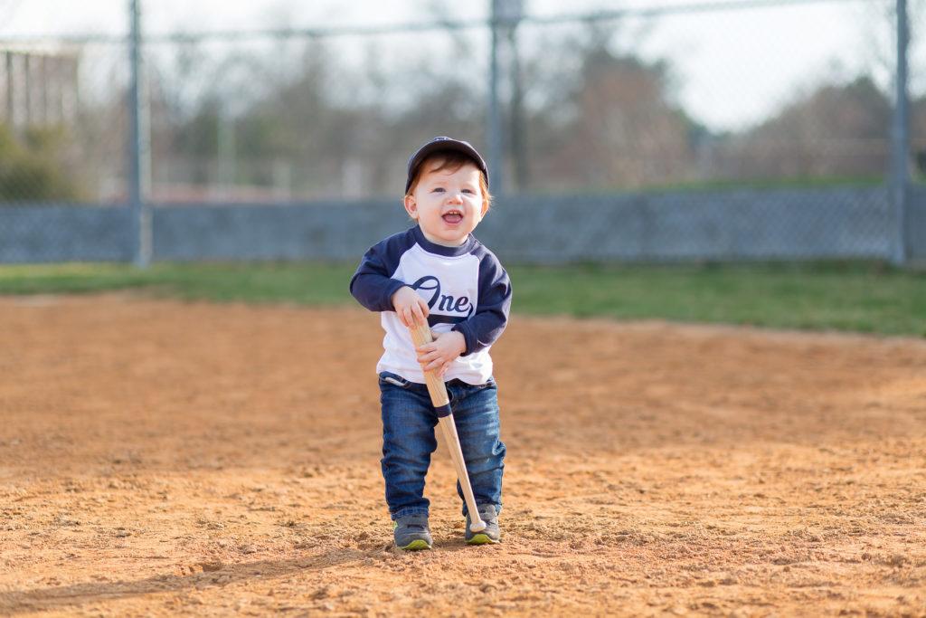 one year old boy holding baseball bat smiling