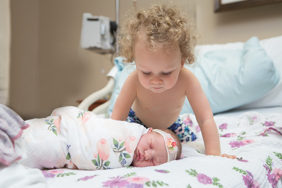 older sibling looking down at newborn sister in hospital