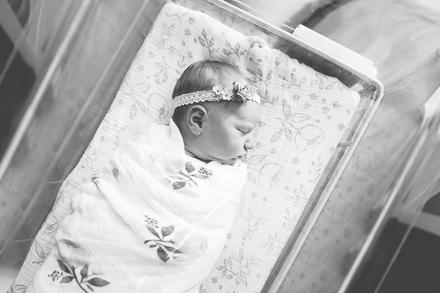 black and white image of newborn baby sleeping in bassinet at hospital