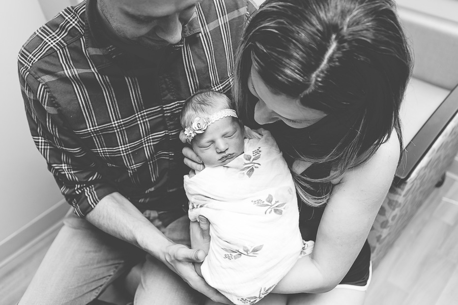 newborn held by parents at hospital