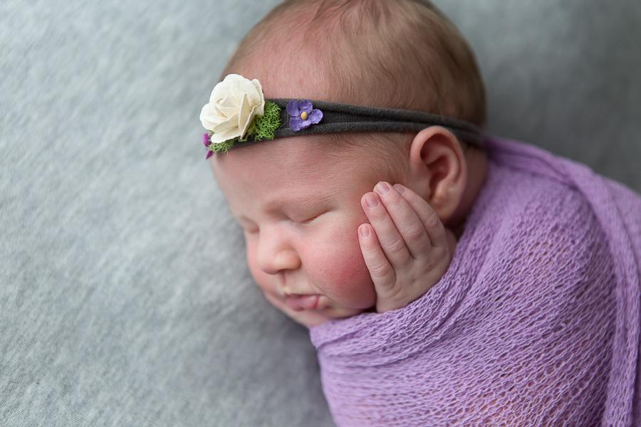 newborn girl swaddled and squishing cheeks