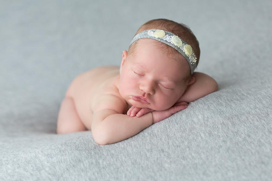 7 day old newborn girl sleeping on grey blanket with grey headband