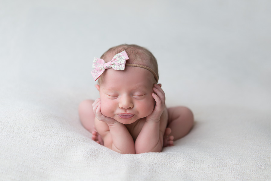 newborn girl frog pose with pink bow