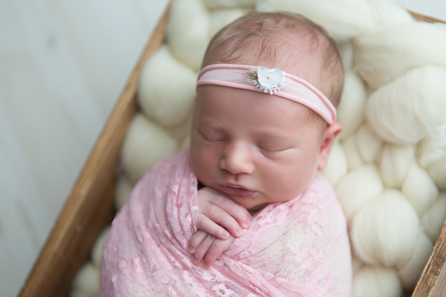 newborn girl with pink headband sleeping swaddled