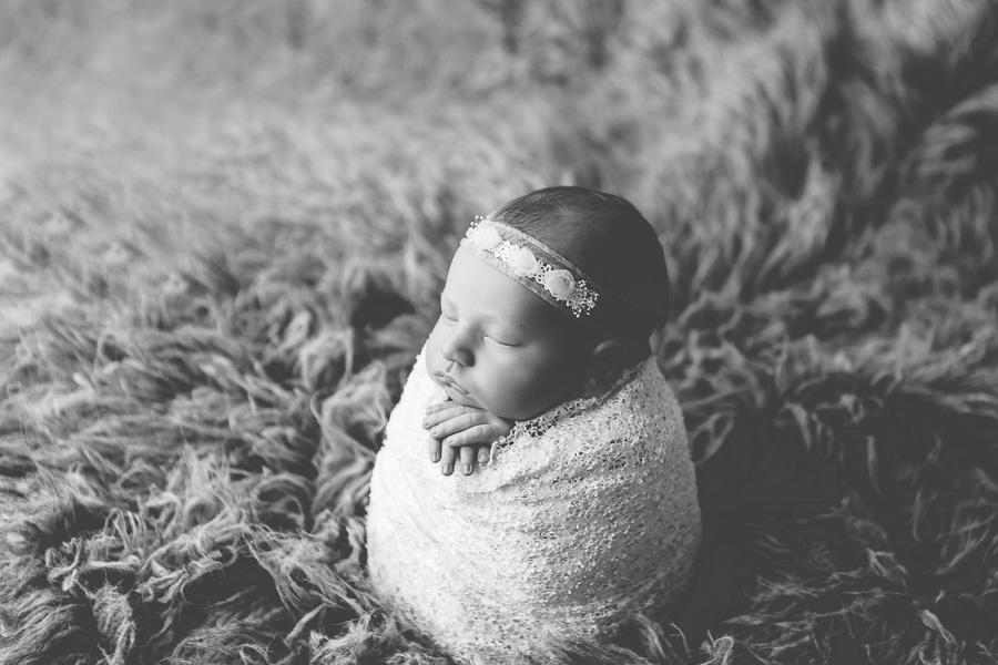 black and white photo of newborn girl swaddled