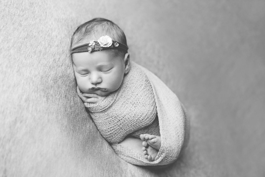 newborn wrapped and sleeping black and white image