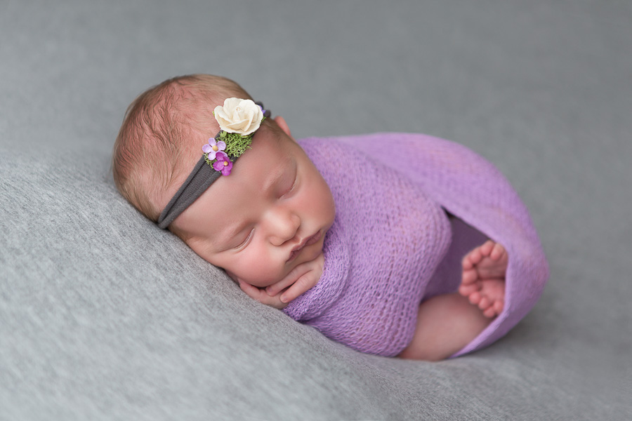 7 day old baby girl in purple swaddle