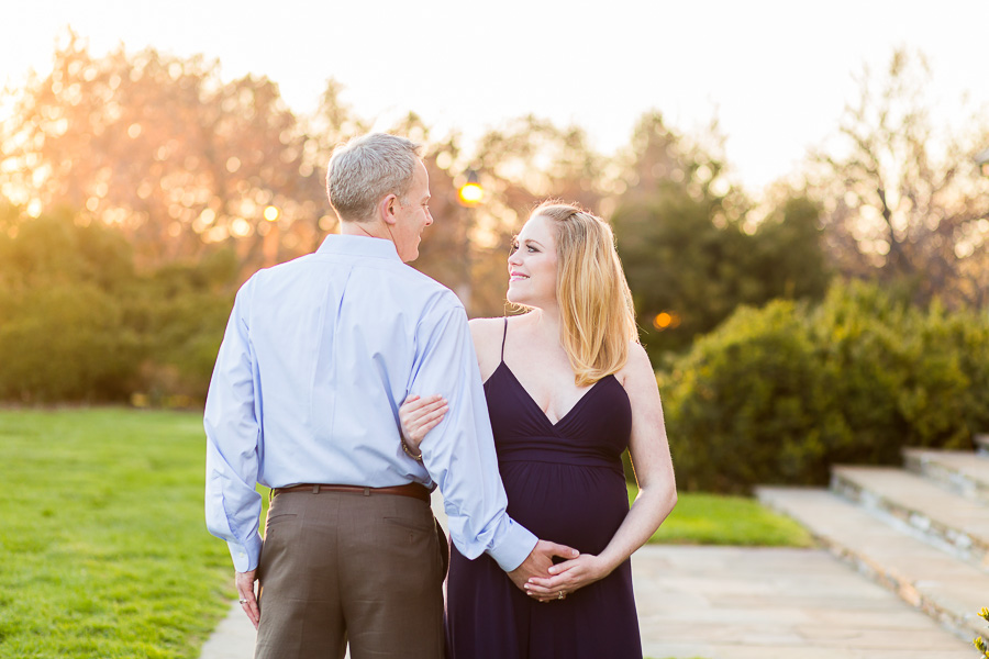 expecting parents looking at each other in front of sunset