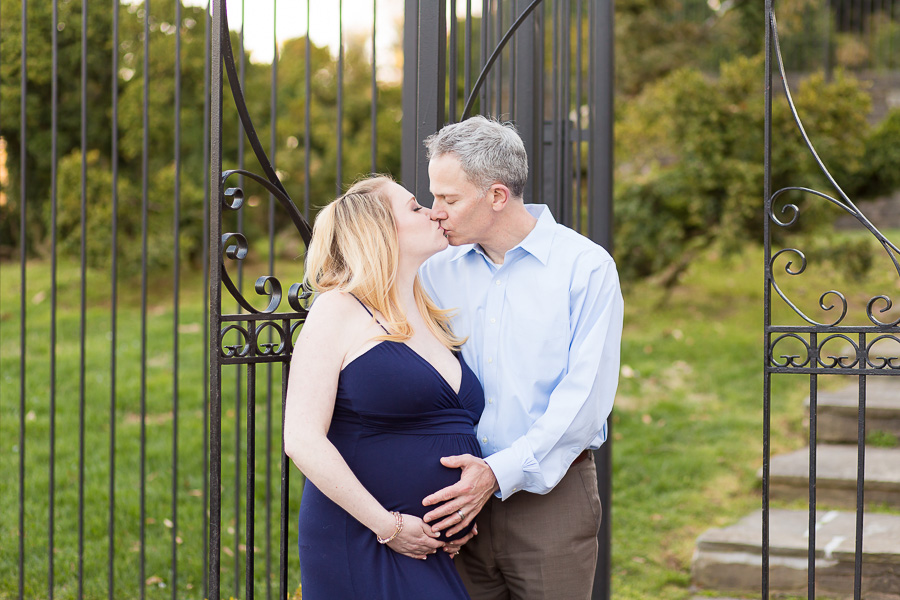 expecting parents holding belly kissing